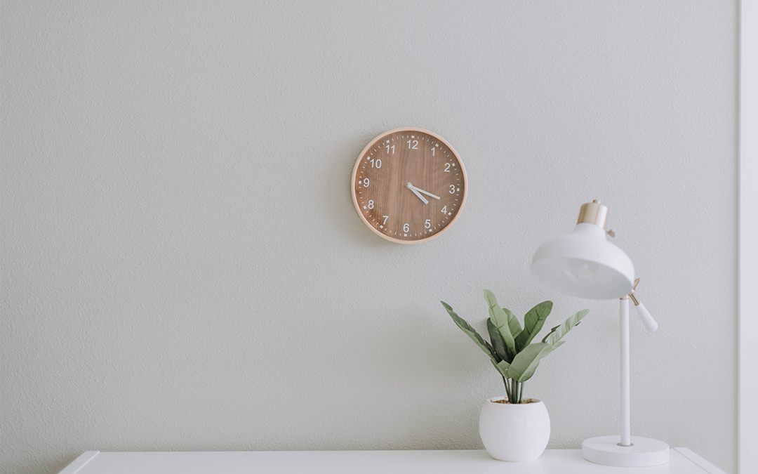 clock on wall plant and lamp on table
